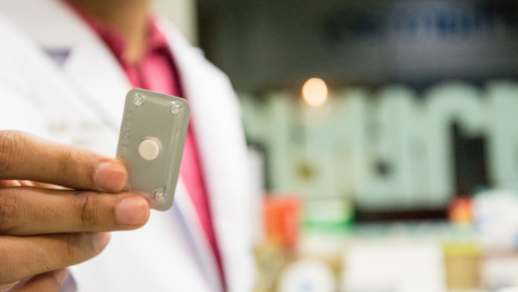 A person with tan skin wearing a lab coat holds contraceptive pills in sterile packaging.